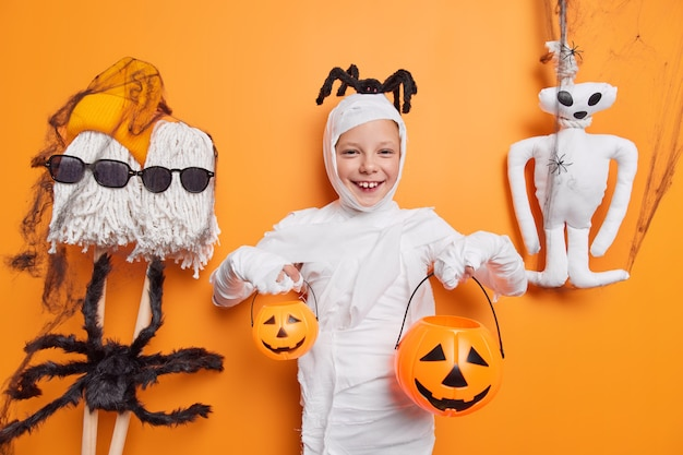 Милая улыбающаяся девушка держит две тыквы на хэллоуин в жутком костюме с пауком на голове позирует на оранжевом