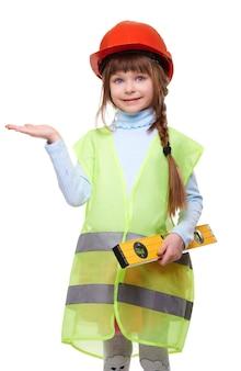 保護ヘルメットと水準器付きの建設ベストのかわいい笑顔の女の子は、彼女の手のひらの上で製品の広告を保持しています