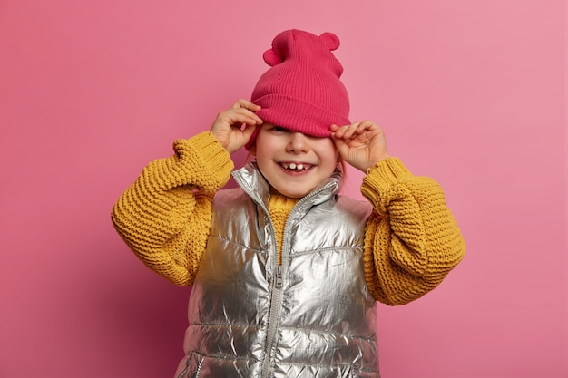 Cute smiling girl looks from under hat, dressed casually, has toothy smile, going crazy, shows two adult teeth, enjoys spare time for playing with friends, isolated on pink wall. happy childhood