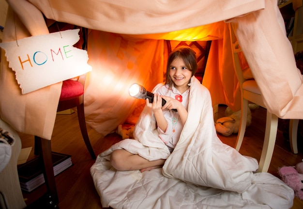 Cute smiling girl playing with flashlight in house made of blankets at bedroom