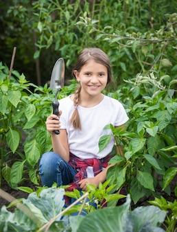 피는 정원에서 흙손으로 포즈를 취하는 귀여운 웃는 소녀