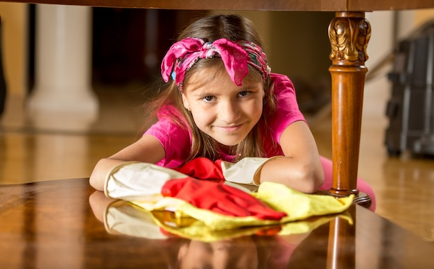 Cute smiling girl in rubber gloves cleaning table by rag