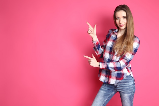Cute smiling girl in a in a shirt and jeans standing on a pink background. lifestyle, emotional, funky. lady shows forefingers of both hands to the side