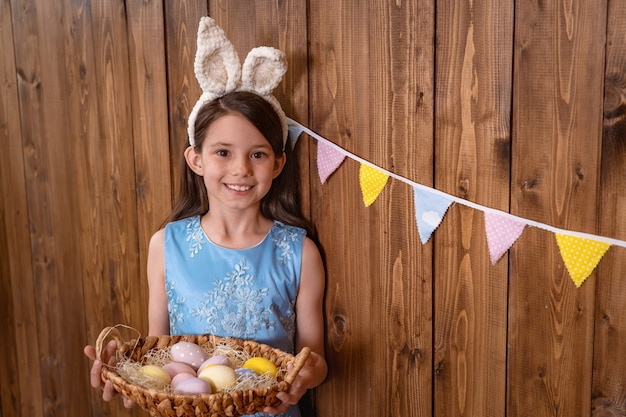 Cute smiling girl stands near wooden wall and holds a basket with colored eggs.
