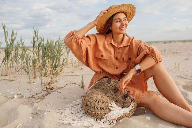 Ragazza sorridente sveglia in vestito di lino alla moda che si distende sulla spiaggia di sera sulla sabbia bianca. cappello di paglia, borsa boho. vacanze mod.