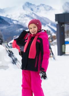 Милая улыбающаяся девушка бросает снежок на горном курорте