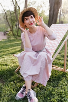 Cute smiling girl in trendy attire enjoying weekend and beautiful nature views, sitting on garden chair