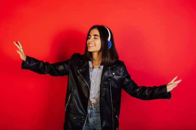 赤い表面に分離されたワイヤレスイヤホンを使用して音楽を聴きながら楽しんでいる目を閉じてかわいい笑顔の女の子。