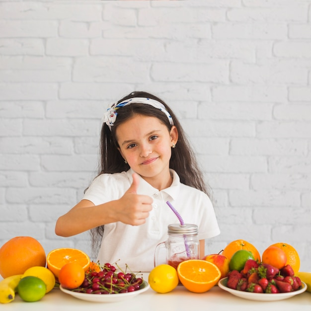 Cute smiling girl with colorful fruits showing thumb up sign