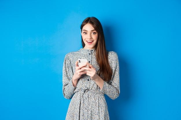 長い自然な髪のかわいい笑顔の女の子、ドレスを着て、スマートフォンを使用して、青に対して立って幸せそうに見えます。