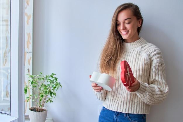 Милая улыбающаяся счастливая очаровательная возлюбленная женщина получила подарок ко дню святого валентина и открывает коробку в форме сердца на день святого валентина