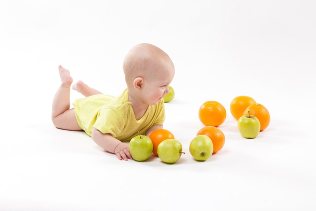 Cute smiling healthy child lies among frui