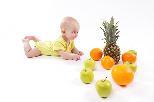 Cute smiling healthy child lies on white among frui