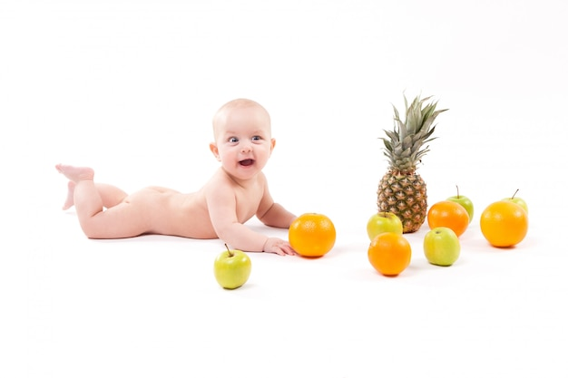Cute smiling healthy child lies on a white background among frui