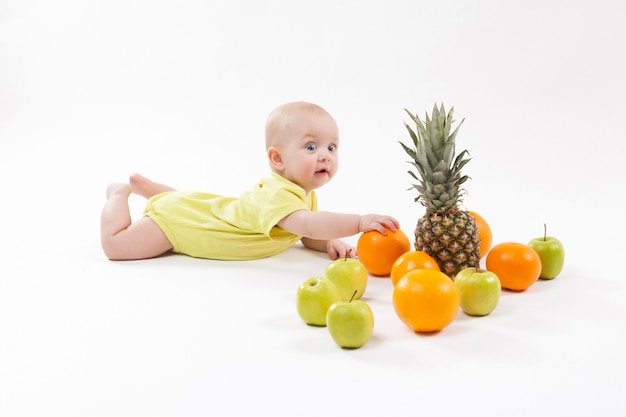 Cute smiling healthy child lies on a white ground among fruit