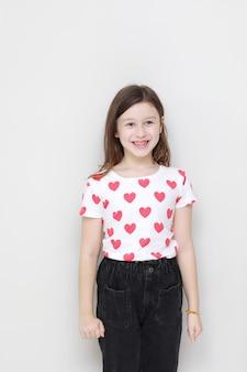 赤いハート、白い背景の上のスタイリッシュな黒のジーンズと白いtシャツのかわいい笑顔の子供の女の子。