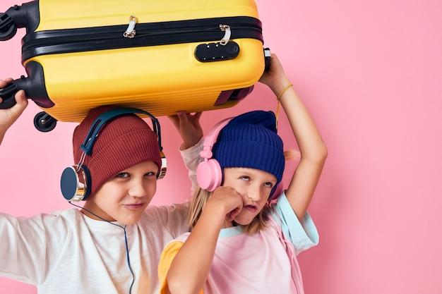 彼の手に黄色のスーツケースピンク色の背景を持つかわいい笑顔の子供たち