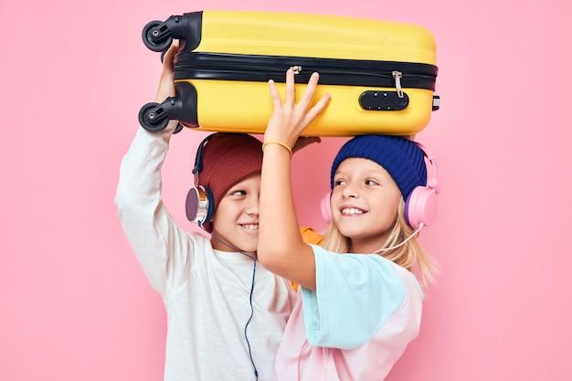 Милые улыбающиеся дети желтый чемодан с наушниками изолированный фон. фото высокого качества
