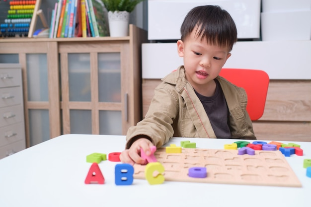 Cute smiling kindergarten boy playing with alphabet blocks, asian children learning english with wooden educational abc toy puzzle