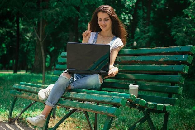 공원에서 벤치에 앉아 노트북을보고 귀여운 웃는 아가씨