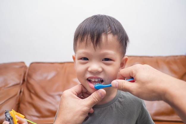 Cute smiling little 3 - 4 years old toddler boy child brushing teeth in the morning at home