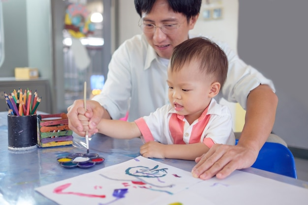 Cute smiling little asian 18 months / 1 year old toddler baby boy child painting with brush and watercolors, businessman father painting with son after working time, creative play for toddlers concept