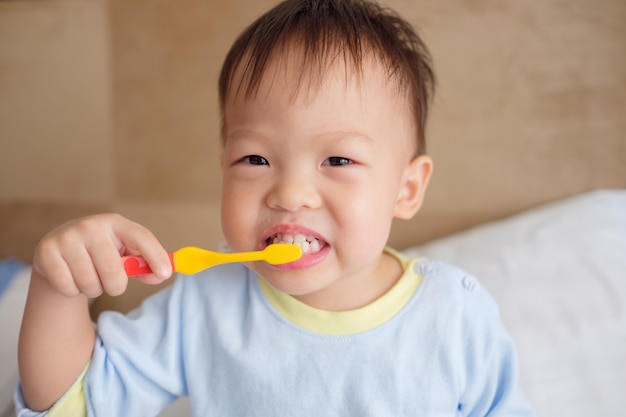 Cute smiling little asian 30 months / 2 year old toddler boy child wearing pajama sitting in bed holding toothbrush and learn to brushing teeth in the morning at home, tooth care for children concept