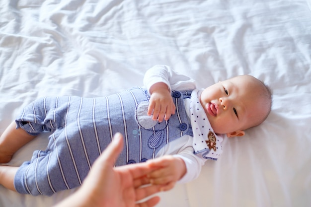 Cute smiling little asian  baby boy child lying in long dungarees holding mothers hand on bed in bedroom at home