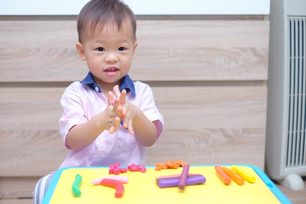 Cute smiling little asian  toddler boy child having fun playing modeling clay at home