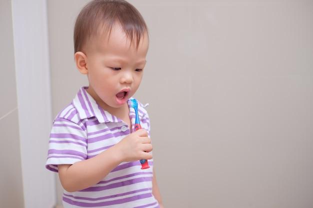 Симпатичный улыбающийся маленький азиатский мальчик-малыш в фиолетовой рубашке, держащий зубную щетку, и учится чистить зубы в ванной дома