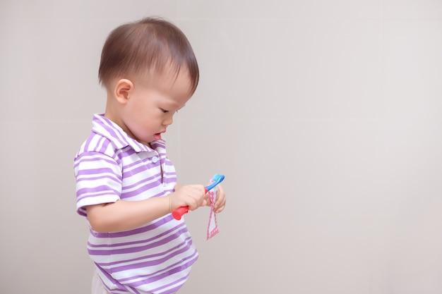 歯ブラシを持って紫色のシャツを着て、自宅のバスルームで歯を磨くことを学ぶかわいい笑顔の小さなアジアの幼児の男の子の子供