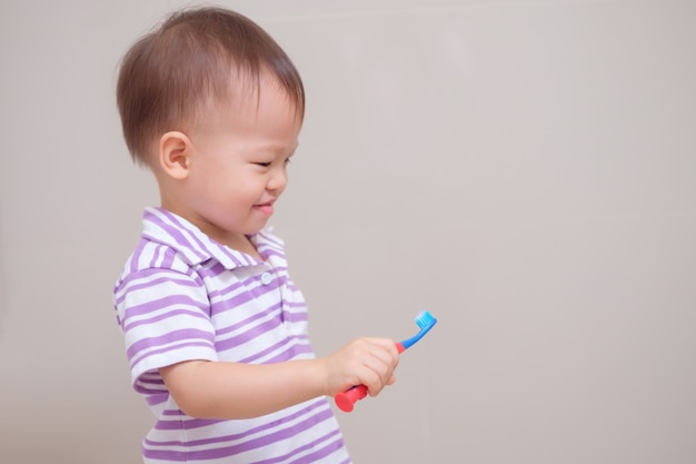 Cute smiling little asian toddler boy child wearing purple shirt holding toothbrush and learn to brushing teeth in bathroom at home