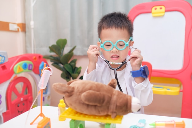 Cute smiling little asian toddler boy in doctor uniform having fun playing doctor with plush toy at home