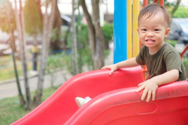 놀이터에서 미끄럼틀에서 놀고 있는 귀여운 웃는 아시아 1세 유아 소년 아이