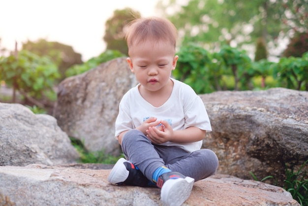 Cute smiling little baby boy child with eyes closed practices yoga and meditating outdoors on nature