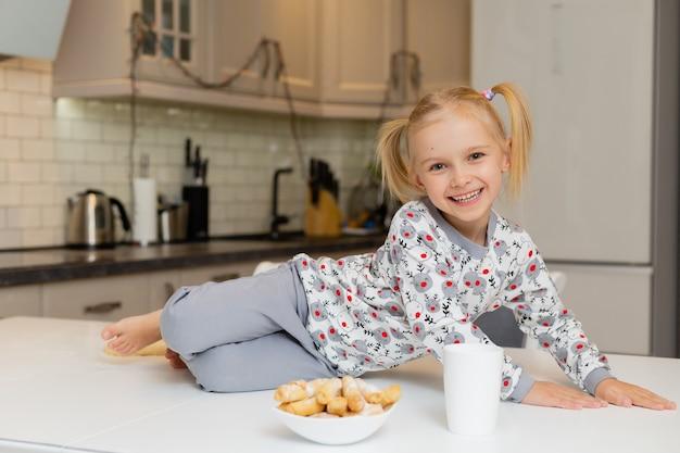 クリスマスのプリントの服を着たかわいい笑顔の小さなブロンドの女の子は、ミルクやお茶のマグカップに座っています