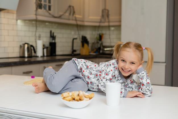クリスマスのプリントの服を着たかわいい笑顔の小さなブロンドの女の子は、ミルクやお茶のマグカップと一緒に座っています