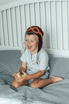 Cute smiling little boy in the cap of the pilot plays on the bed with a small wooden plane