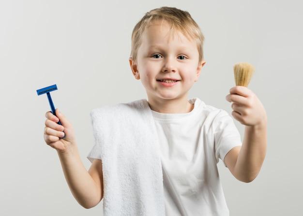 Cute smiling little boy holding razor and shaving brush standing against white background