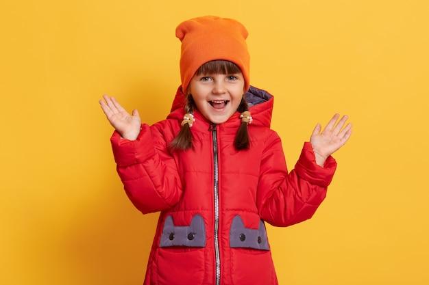노란색 벽에 고립 된 그녀의 손을 키우는 귀여운 웃는 작은 아이, 열린 된 mouthcap으로 앞에서 보인다.