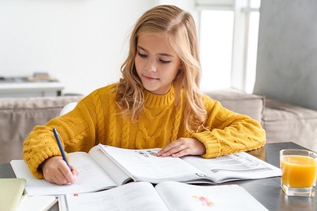 Милая улыбающаяся маленькая девочка делает домашнее задание, сидя за столом в гостиной