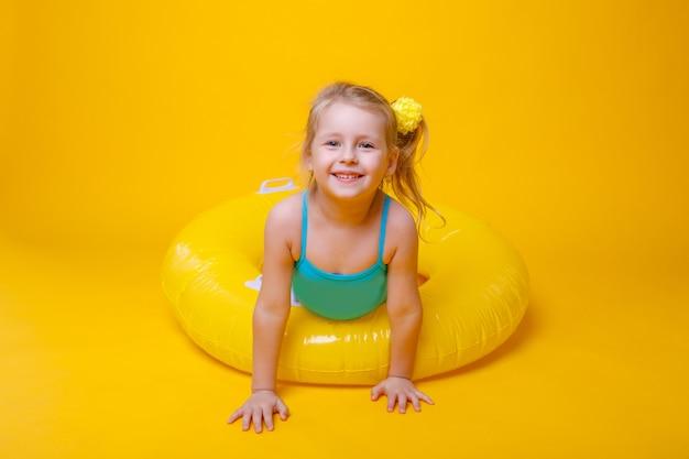 黄色に分離されたゴム製のリングと水着でかわいい笑顔女の子