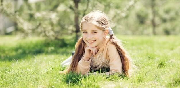 草の上に横たわるかわいい笑顔の女の子