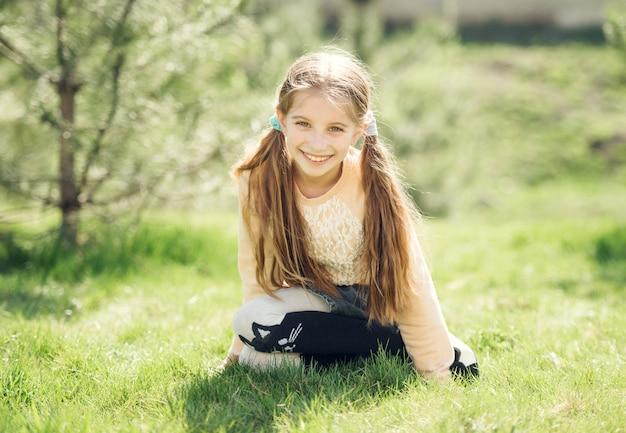 草の上に座って笑顔かわいい女の子