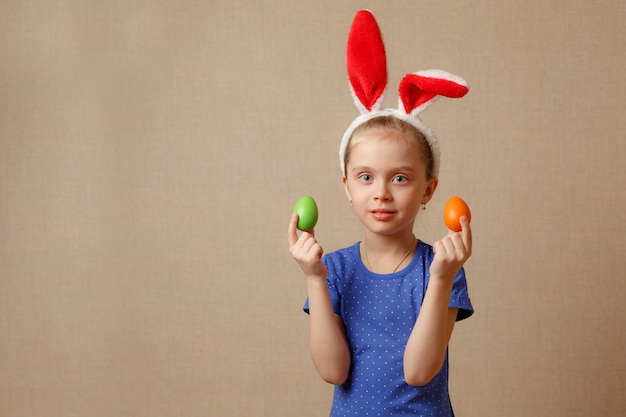 Cute smiling little girl with colorful easter eggs. happy easter