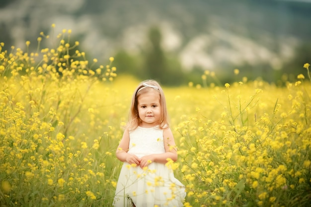 Cute smiling little girl with flower wreath on the meadow at the farm. portrait of adorable small kid outdoors. midsummer. earth day