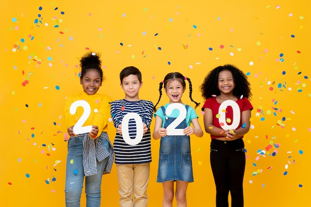 Cute smiling mixed race children showing numbers 2020 celebrating new year