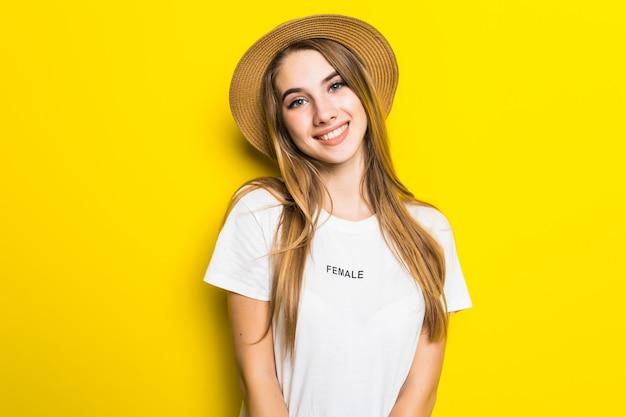 Симпатичная улыбающаяся модель в белой футболке и шляпе на оранжевом фоне с забавным лицом