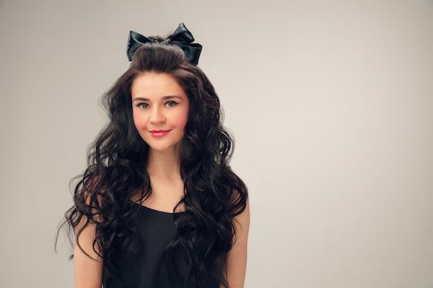 かわいい笑顔。灰色のスタジオで美しい若い女性の肖像画