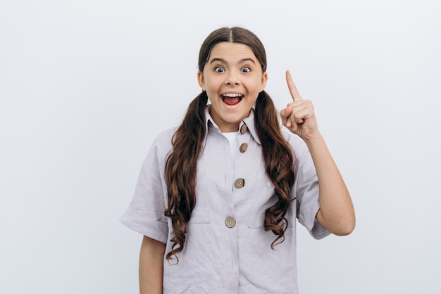 귀엽고, 웃고, 긍정적인 십대 소녀가 손가락을 들어올렸습니다. 소녀는 아이디어가 있고 흰색 배경에 기뻐합니다